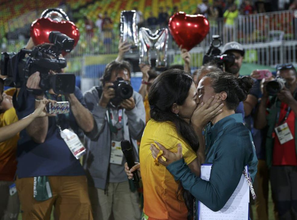 Rugby player Isadora Cerullo of Brazil kisses Marjorie, a volunteer, after receiving her wedding proposal on the sidelines of the women's rugby medal ceremony