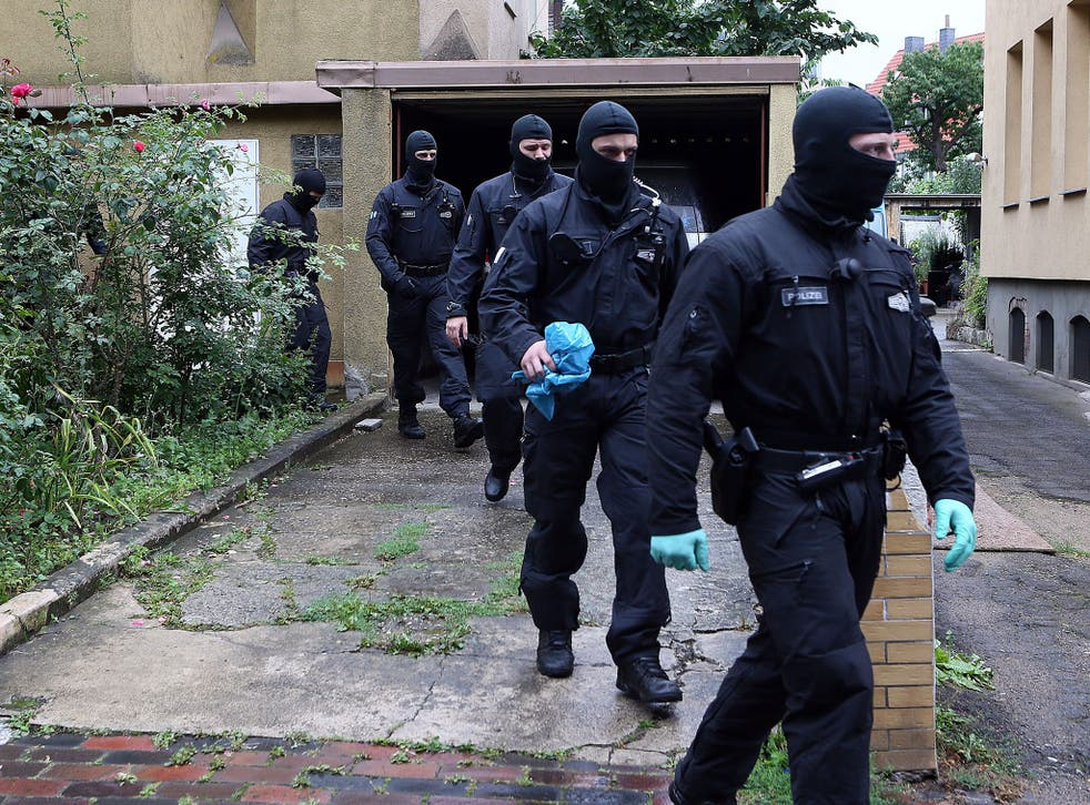 Masked police forces leave after searching a house in Hildesheim, Germany, 10 August 2016.