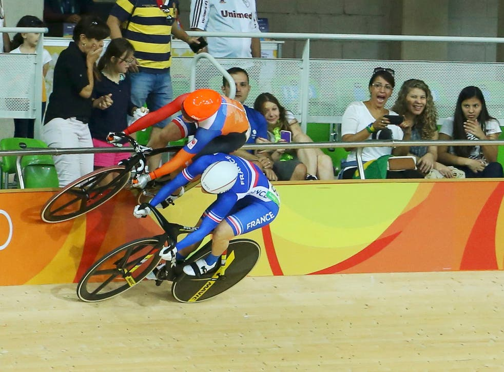 Laurine van Riessen of the Netherlands (in orange) avoids a crash with Virginie Cueff of France (in blue) during the women's keirin first round cycling track event