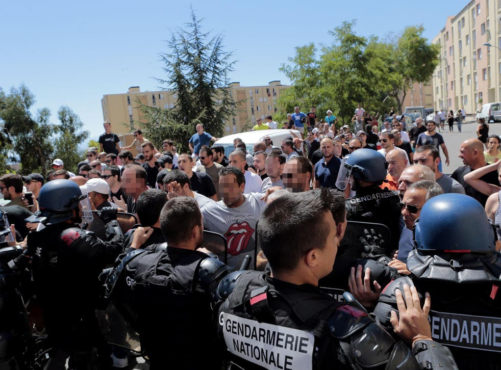 Hundreds walk into the cite des Monts surrounded by policemen in Lupino on August 14, 2016 in Bastia on the French Mediterranean island of Corsica