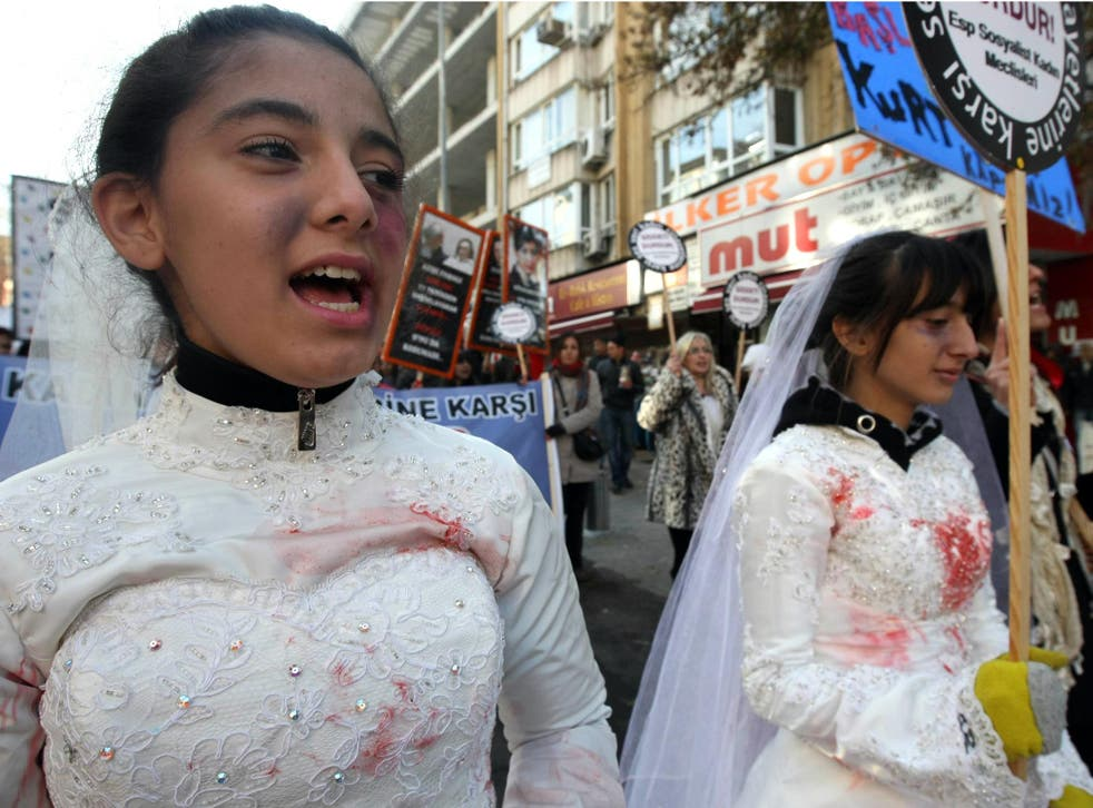 Turkish women, wearing wedding dressed and covered with fake bruises, at a protest against rape, killings and domestic violence against women