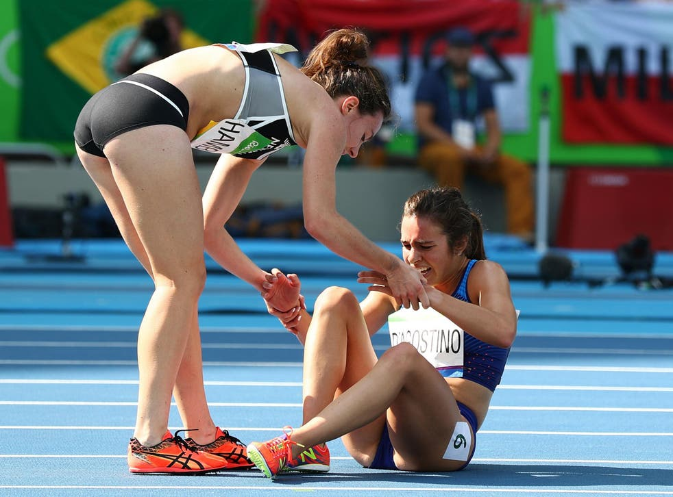 Abbey D'Agostino of the United States (R) is assisted by Nikki Hamblin of New Zealand after a collision during the Women's 5000m Round 1