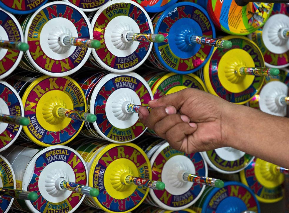 An Indian kite-maker removes a reel of kite string to be used at his shop ahead of Independence Day celebrations in New Delhi