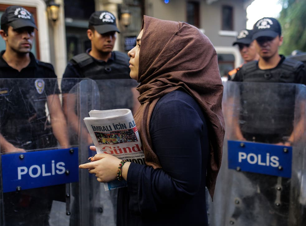A woman holds a 'Ozgur Gundem' newspaper in front of a police barricade on August 16, 2016 in Istanbul.