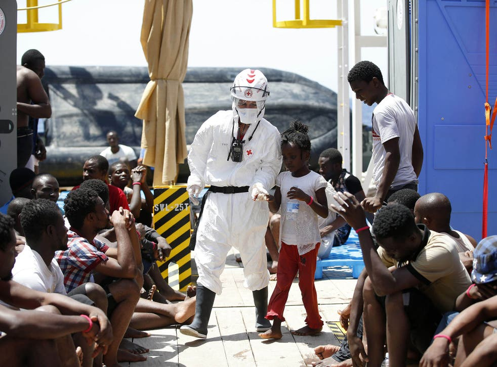 A Red Cross worker with child refugees in Sicily after a rescue operation on Thursday