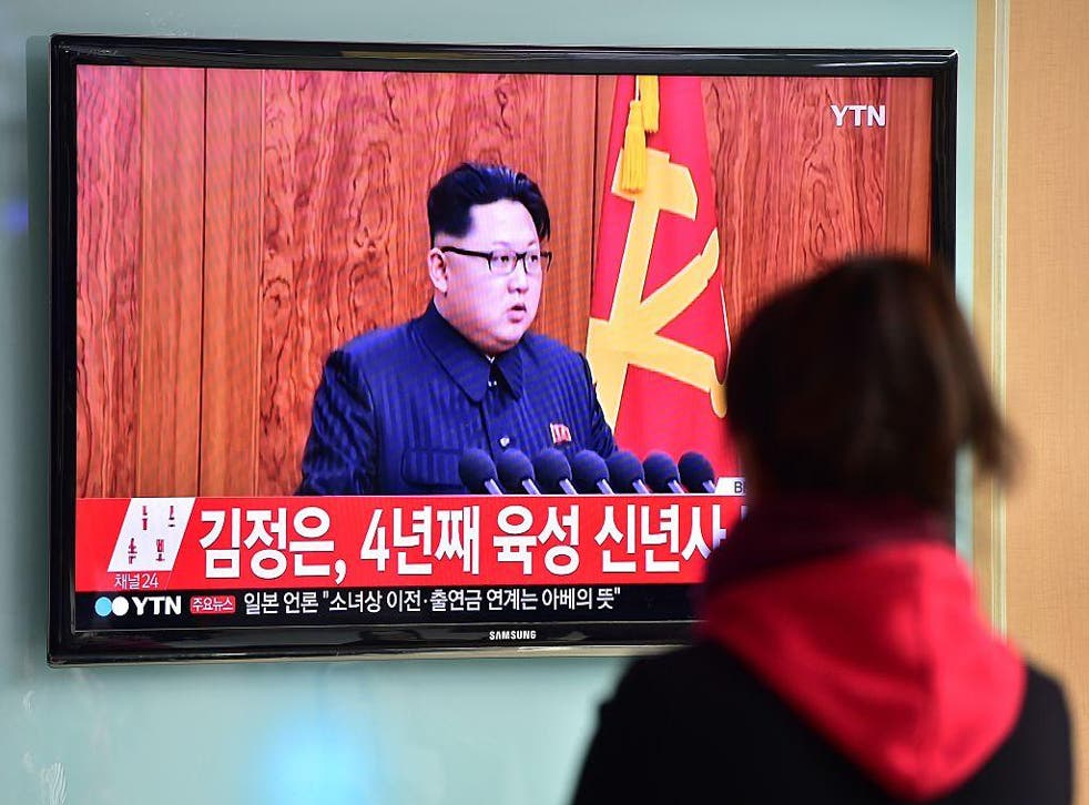 A woman watches a televised broadcast of North Korean leader Kim Jong-Un's New Year speech, at a railroad station in Seoul on January 1, 2016.