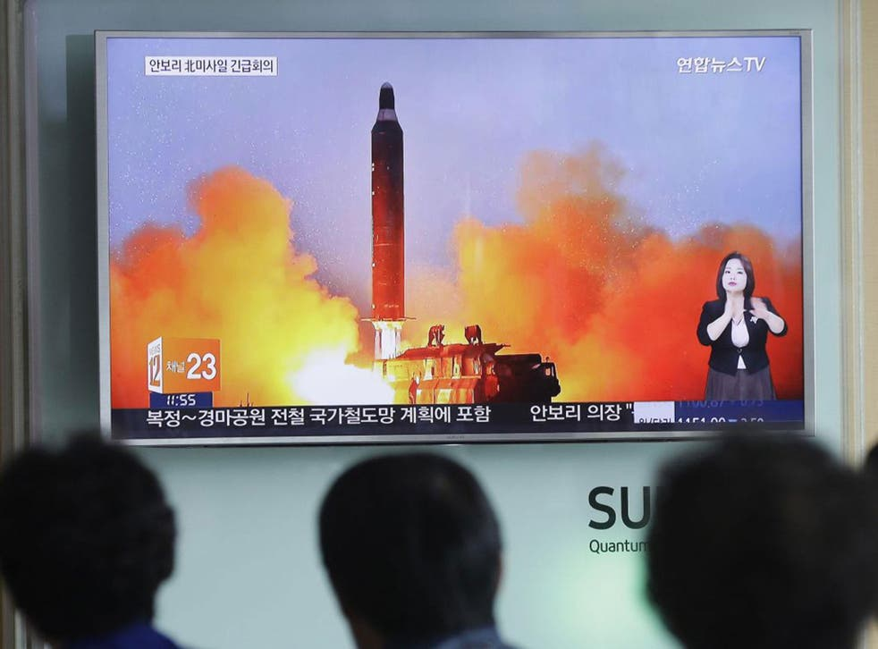 People watch a TV news channel airing an image of North Korea's ballistic missile launch in June. North Korea has made nuclear threats before