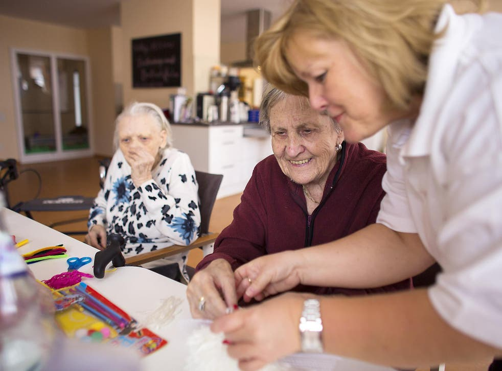 Nurse Doret Kohl (R) helps day guest Margot (C) to make handcrafts in the geriatric day care facility of the German Red Cross (DRK, or Deutsches Rotes Kreuz) at Villa Albrecht on March 11, 2013 in Berlin, Germany