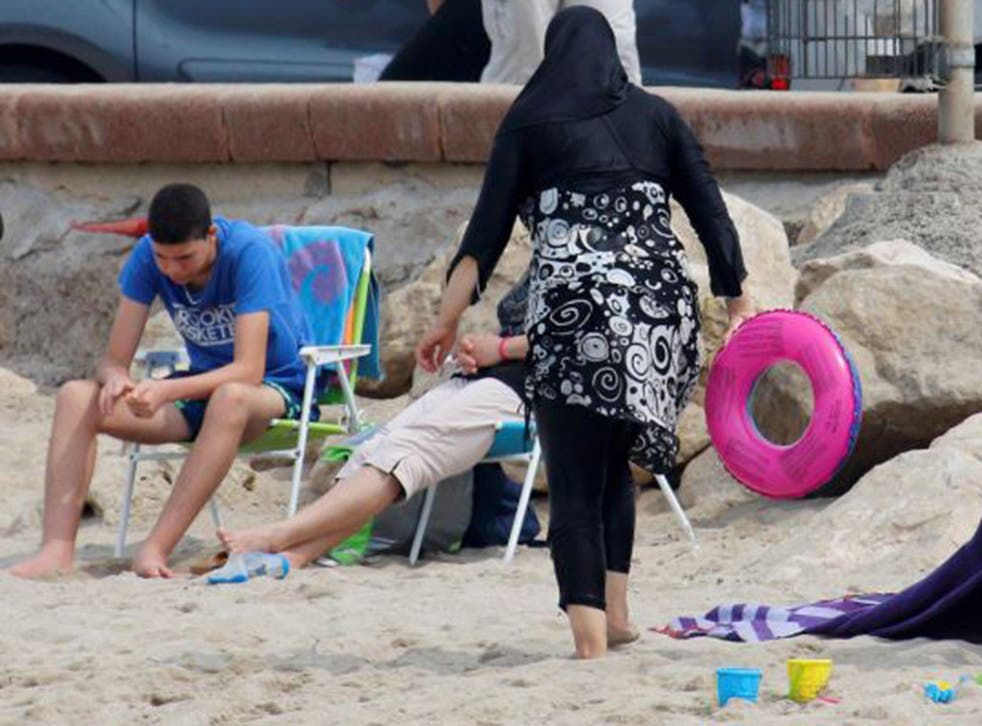A woman wears a burkini on a beach in Marseille