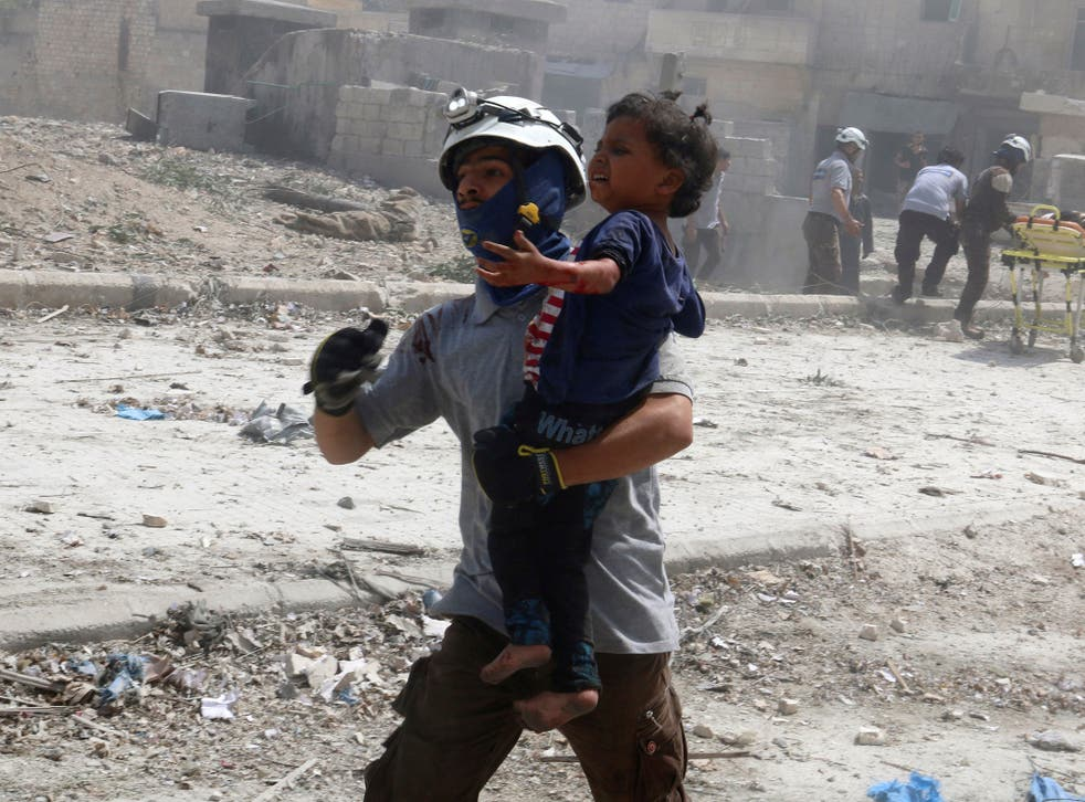 A man carries an injured child after the bombing in the rebel held Bab al-Nayrab neighborhood of Aleppo
