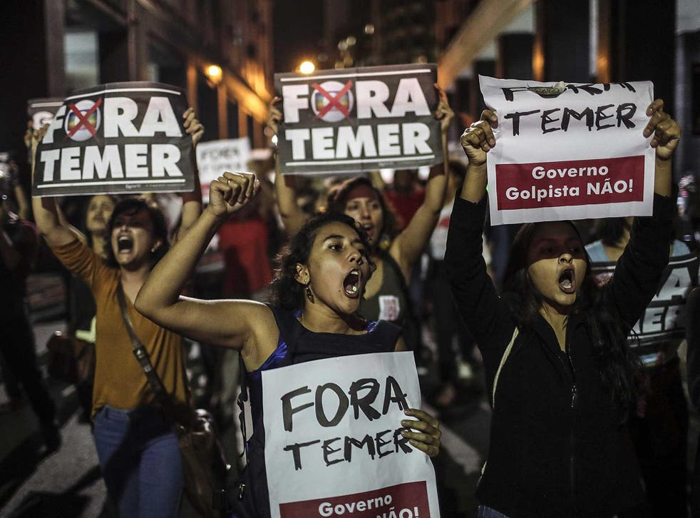 Protesters in Brazil hold signs saying 'Out with Temer'
