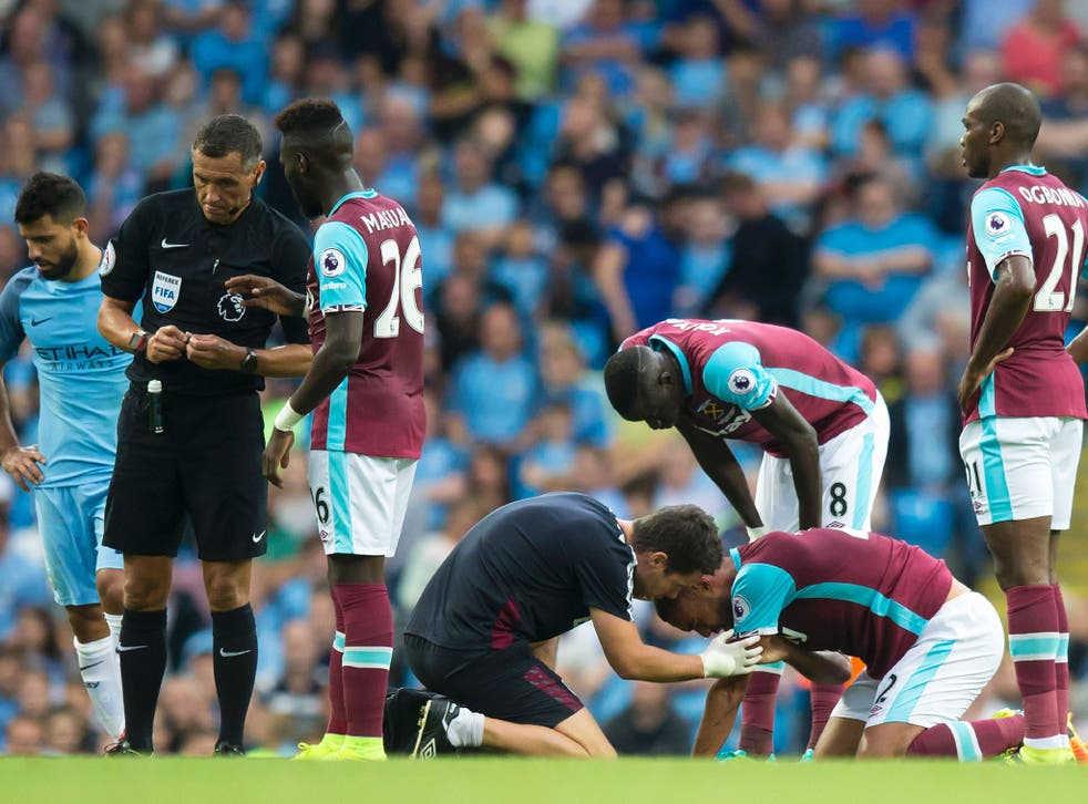 Winston Reid receives treatment after his clash with Sergio Aguero during Sunday's game