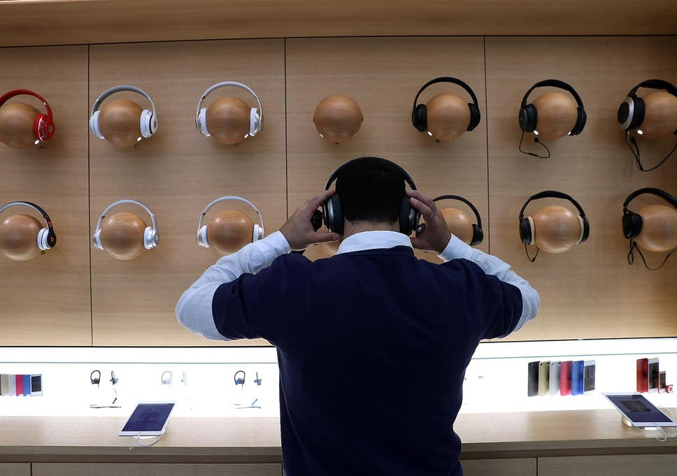 An Apple Store employee tries on a pair of headphones during a press  preview of the 2fdff7b2c
