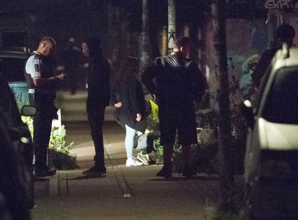 Policemen ask questions to people after a shooting in  Christiania, Copenhagen on 1 September.