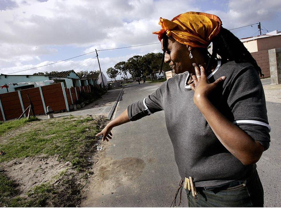 Nyanga resident Pam Mokoena points out the spot where her brother was gunned down outside her house in the Nyanga township, on the outskirts of Cape Town