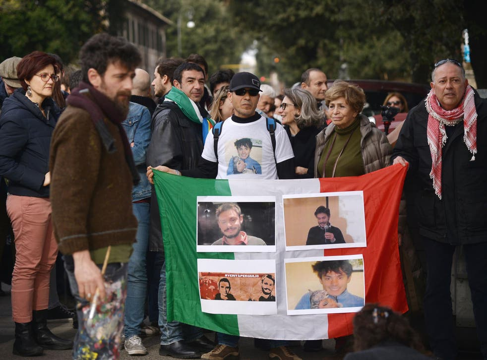 People hold an Italian flag with photos of Giulio Regeni during a demonstration in front of the Egypt's embassy in Rome on 25 February
