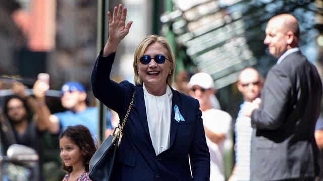 """11/09/2016: Hillary Clinton waves to the press as she leaves her daughter's apartment building after resting in New York. Clinton departed from a remembrance ceremony on the 15th anniversary of the 9/11 attacks after feeling """"overheated,"""" but was later doing """"much better,"""" her campaign said"""