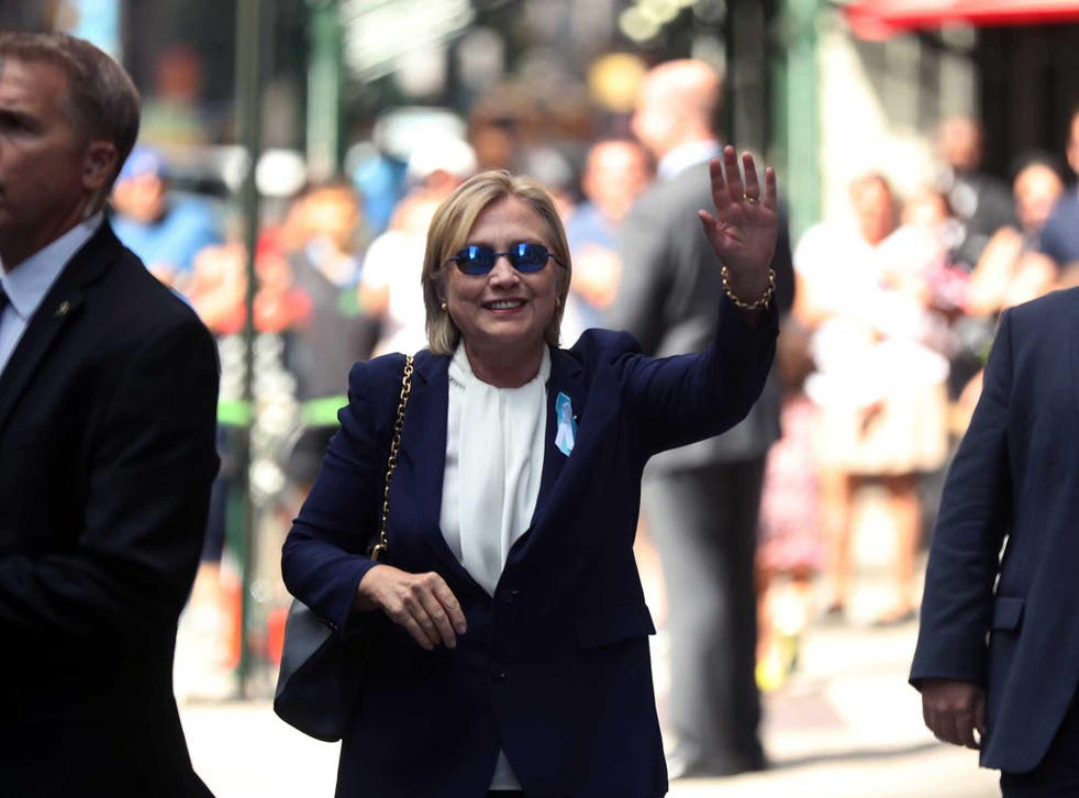 Hillary Clinton waves after leaving an apartment building in New York