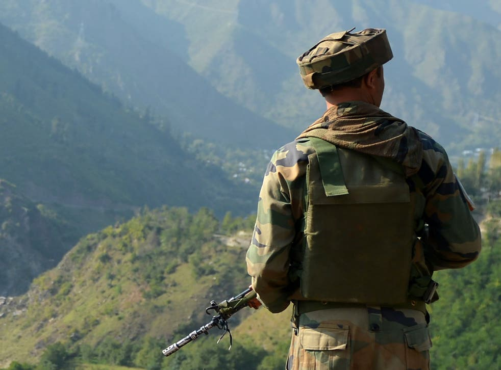 An Indian army soldier looks towards the site of a gunbattle between Indian army soldiers and rebels inside an army brigade headquarters near the border with Pakistan, known as the Line of Control (LoC), in Uri on September 18, 2016