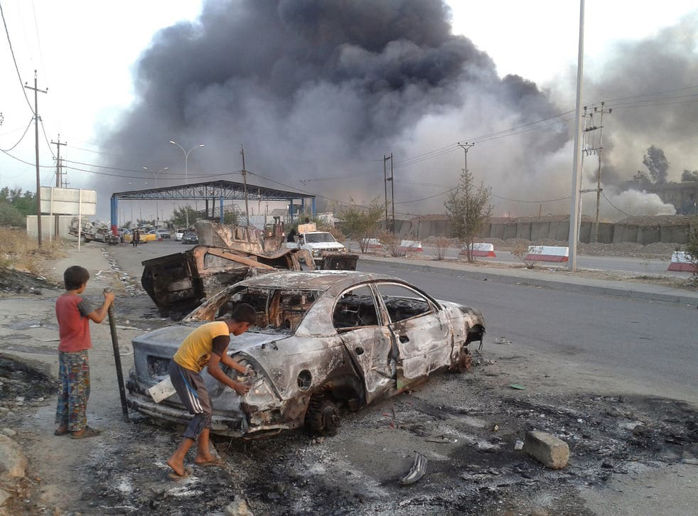 Civilian children stand next to a burnt vehicle during clashes between Iraqi security forces and Islamic State in Mosul, Iraq