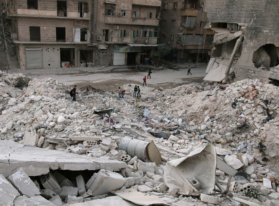 People walk on the rubble of damaged buildings in the rebel held area of al-Kalaseh in Aleppo on 29 September