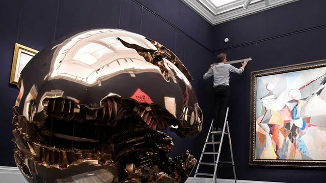 "An employee hangs works of art with ""Grand Teatro"" by Marino Marini (R) and bronze sculpture ""Sfera N.3"" by Arnaldo Pomodoro seen ahead of a  Contemporary Art auction on 7 October, at Sotheby's in London"