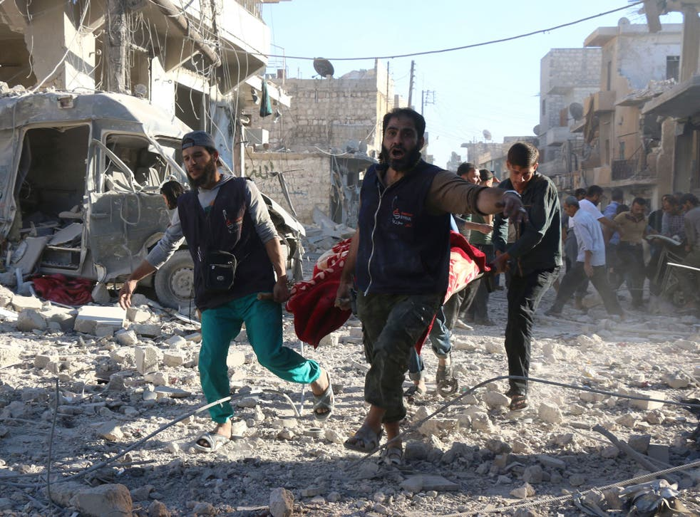 Volunteers carry an injured person after an air strike in Aleppo