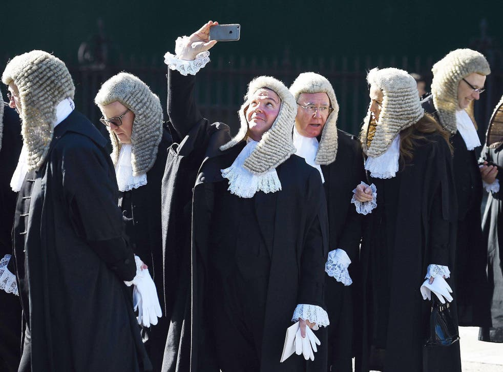 A judge takes a selfie as he follows a procession of judges in to the houses of parliament in London