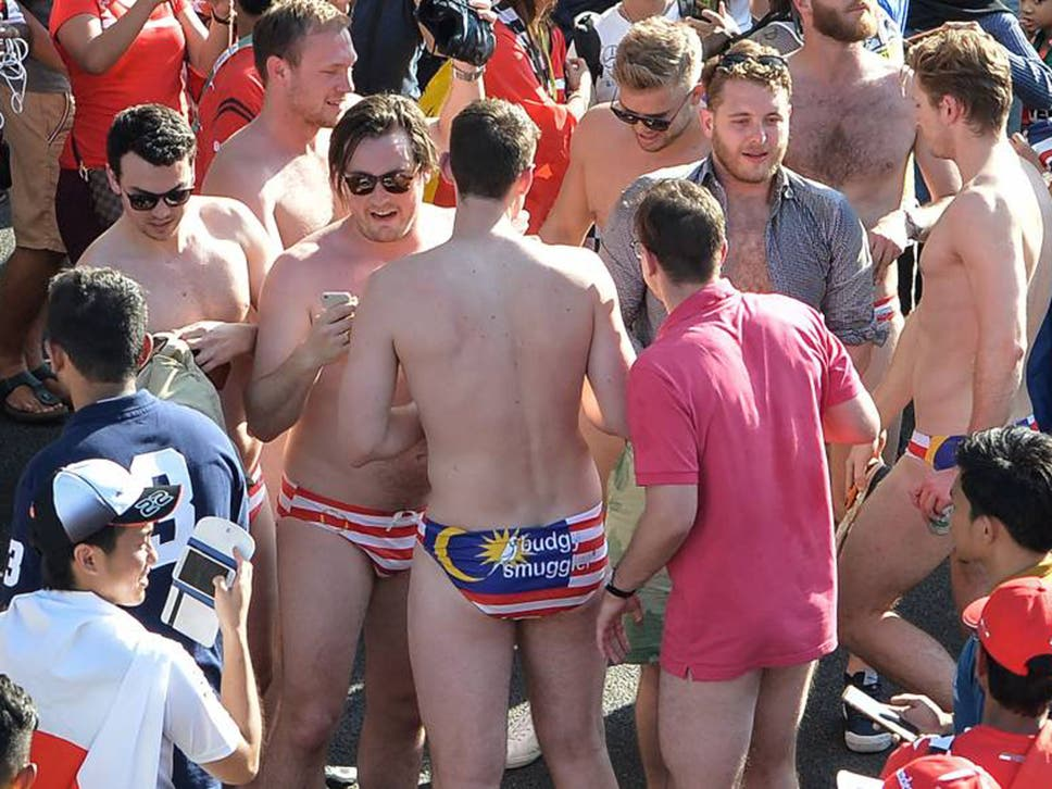 Australian spectators wearing swimwear bearing the Malaysian flag party during the Malaysian Grand Prix
