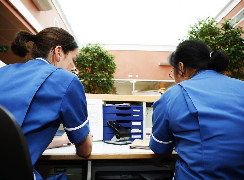 Two nurses sitting behind reception desk in London hospital