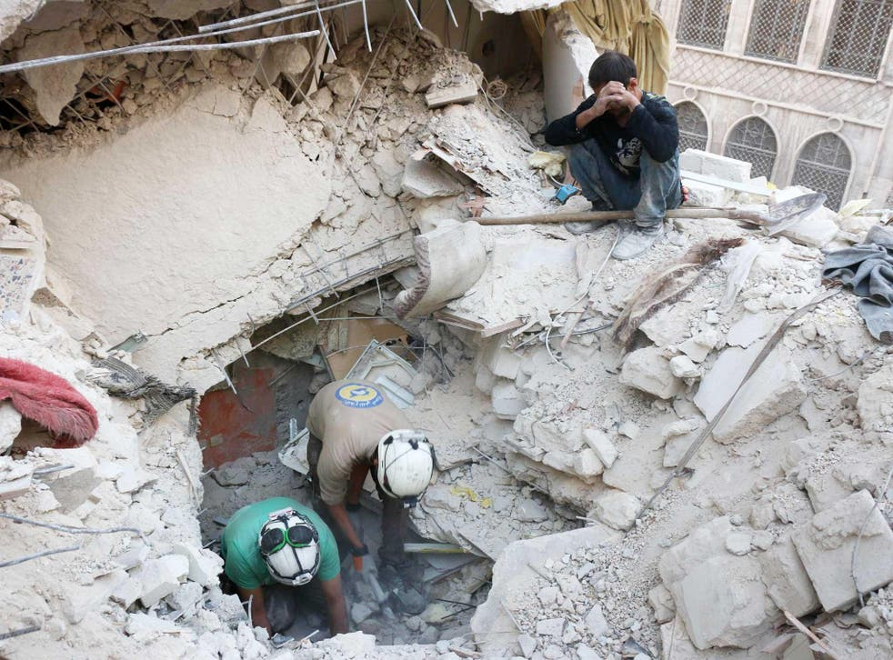 Syrian civil defence volunteers, known as the White Helmets, search for victims amid the rubble of destroyed buildings following a government forces air strike on the rebel-held neighbourhood of Bustan al-Basha in the northern city of Aleppo