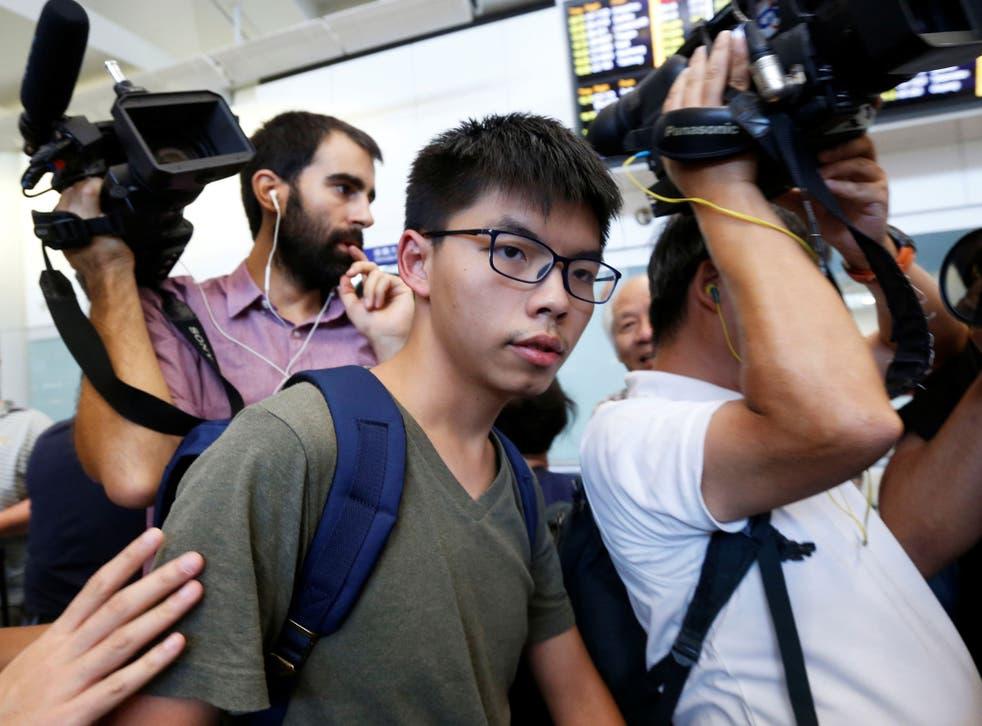 Pro-democracy activist Joshua Wong is surrounded by journalists upon his arrival at Hong Kong Airport in Hong Kong