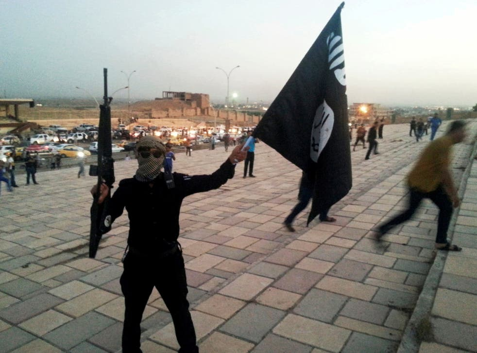 An Isis fighter brandishes a flag and automatic rifle on a street in Mosul
