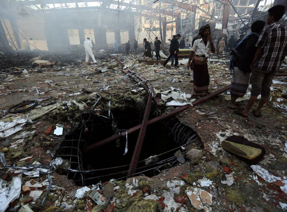 Yemenis inspect the site of Saudi-led airstrikes that hit a funeral ceremony in Sanaía