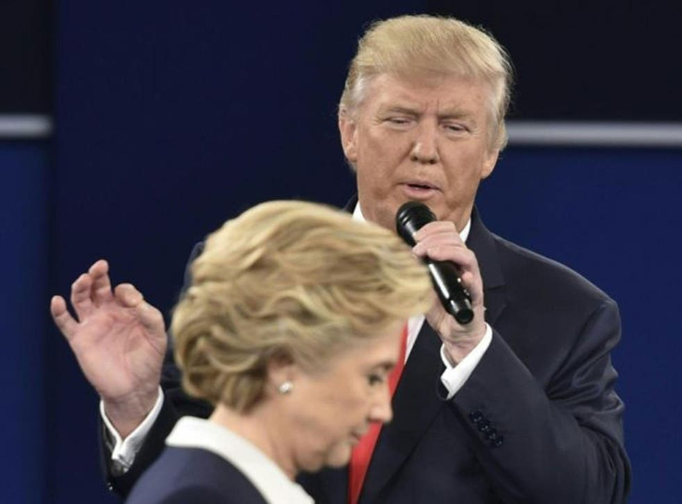 Republican presidential candidate Donald Trump speaks as Democratic presidential candidate Hillary Clinton walks past during the second presidential debate at Washington University in St. Louis, Missouri on 9 October, 2016