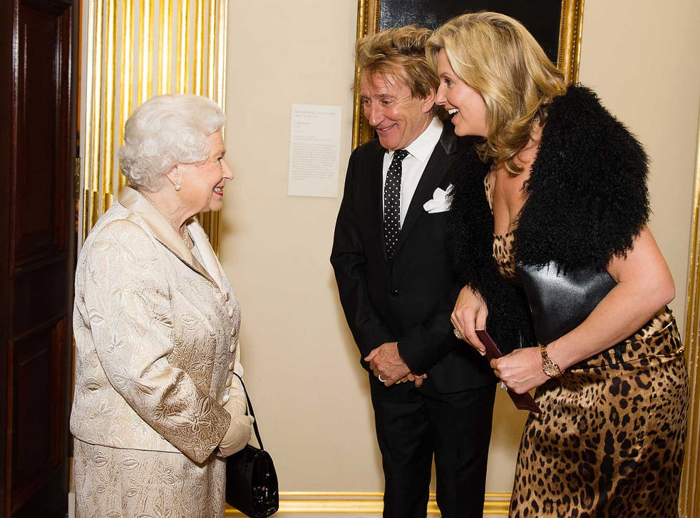 Queen Elizabeth II greets Sir Rod Stewart and wife Penny Lancaster after he was awarded a knighthood in recognition of his services to music and charity earlier in the day as they attend a reception and awards ceremony at Royal Academy of Arts