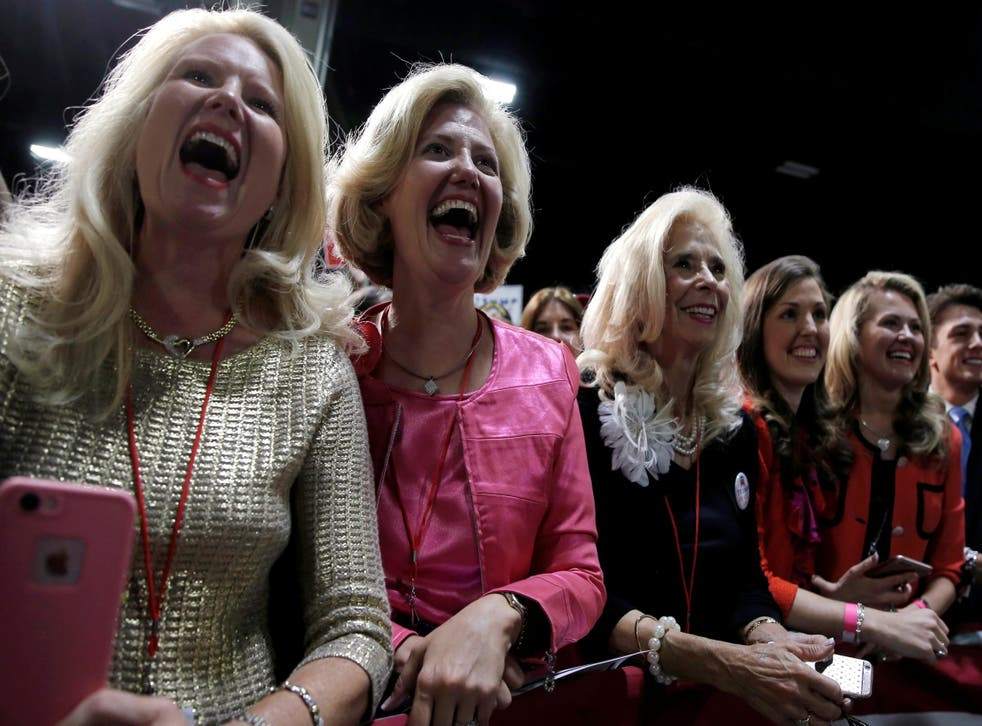 Supporters of Republican US presidential nominee Donald Trump cheer as he takes the stage at a campaign rally in Charlotte, North Carolina