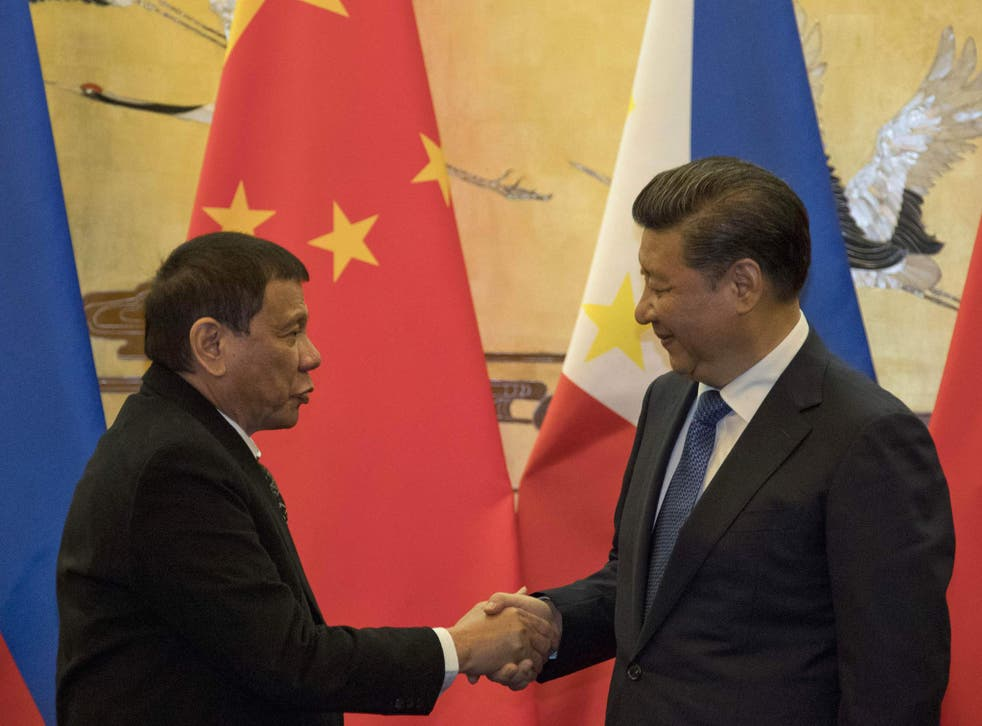 Mr Duterte, left and Chinese president Xi Jinping shake hands during the Beijing visit