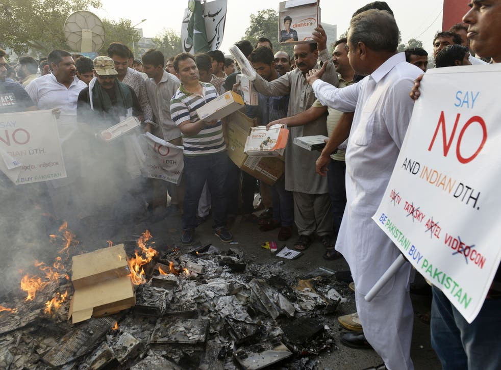 Pakistani shopkeepers and traders burn Indian products including TV transmission systems and CDs during a demonstration in Lahore on October 8, 2016