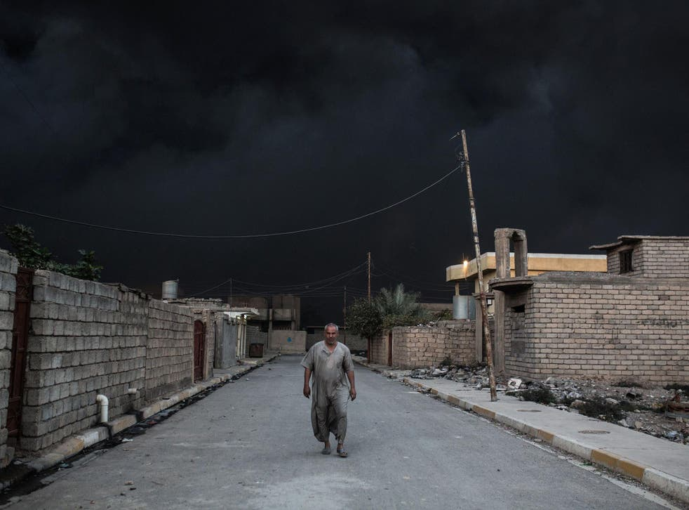 An Iraqi man walks on a street covered with smoke after an oil fire was set ablaze in the Qayyarah area, south of Mosul