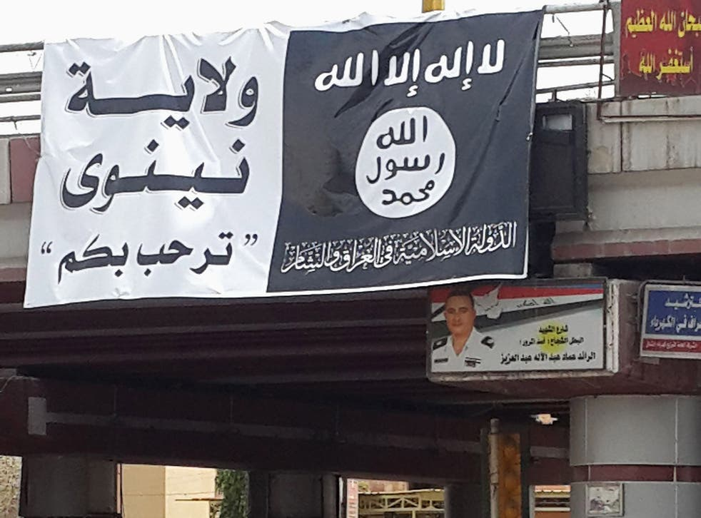 A flag belonging to the Islamic State in Iraq and the Levant (ISIL) along a street in the city of Mosul