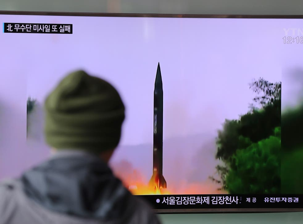 A man watches a TV news program showing a file image of missile launch conducted by North Korea, at the Seoul Railway Station in Seoul, South Korea
