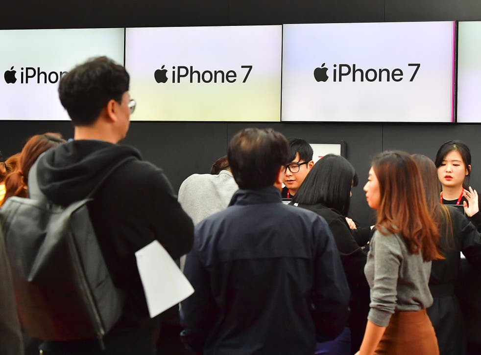 People wait in line to buy new iPhone models at a telecom shop in Seoul, South Korea