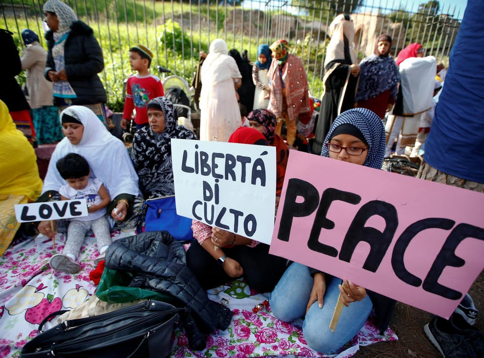 Children hold signs saying, 'peace', 'love' and 'open the mosques'