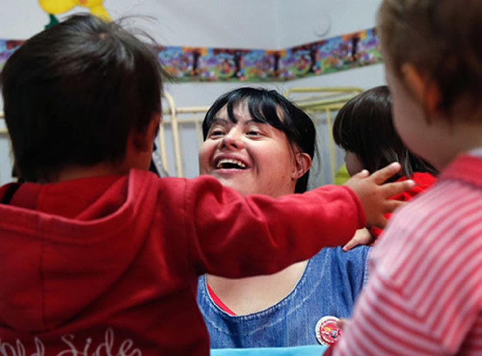 Noelia Garella, a nursery school teacher born with Down syndrome, plays with children at the Jeromito kindergarten in Cordoba, Argentina
