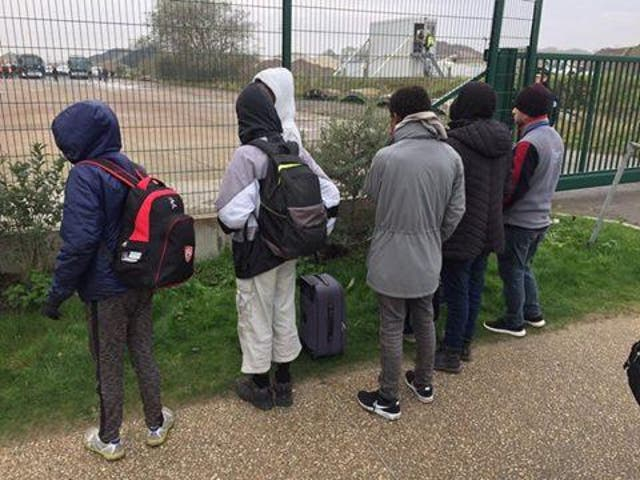 Six of the children, aged 13 and under, stand with their packed bags in Calais waiting for the bus that will transport them to the UK