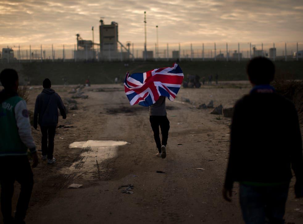 A man runs with a British flag during the mass evacuation of the Calais 'Jungle'