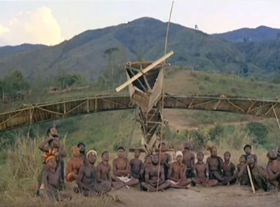 Members of the cargo sect sitting next to a replica they built.
