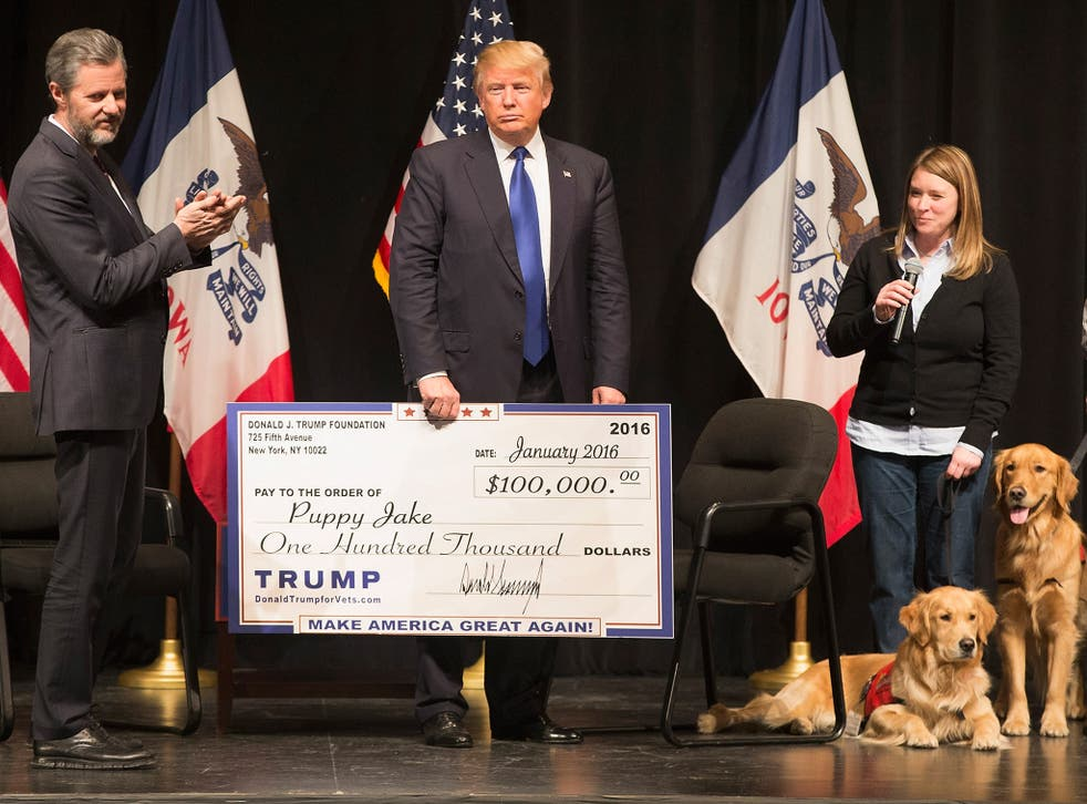 Donald Trump presenting a cheque for $100,000 to a charity that provides dogs for wounded veterans. He gave over $250,000 for the renovation of a fountain outside his Plaza Hotel.