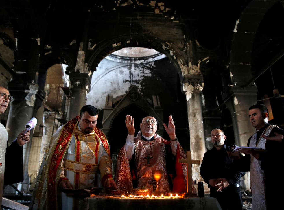 Iraqi priests hold Sunday mass at a church in Qaraqosh last month, after the town was recaptured from Isis